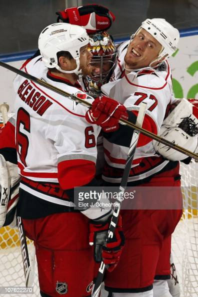 Goaltender Justin Peters of the Carolina Hurricanes is surrounded by teammates Tim Gleason and Joe Corvo after beating the Florida Panthers 43 at the...