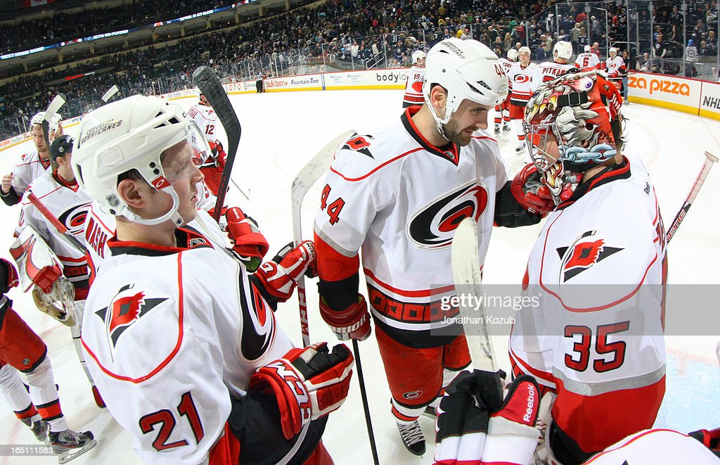 Goaltender Justin Peters #35 of the Carolina Hurricanes receives congratulations from teammates <a gi-track='captionPersonalityLinkClicked' href=/galleries/search?phrase=Jay+Harrison&family=editorial&specificpeople=714374 ng-click='$event.stopPropagation()'>Jay Harrison</a> #44 and <a gi-track='captionPersonalityLinkClicked' href=/galleries/search?phrase=Drayson+Bowman&family=editorial&specificpeople=4111563 ng-click='$event.stopPropagation()'>Drayson Bowman</a> #21 after backstopping the team to a 3-1 victory over the Winnipeg Jets at the MTS Centre on March 30, 2013 in Winnipeg, Manitoba, Canada.