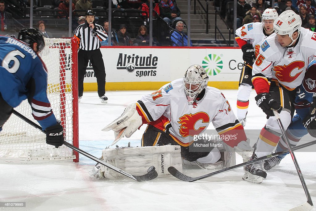 Goaltender <a gi-track='captionPersonalityLinkClicked' href=/galleries/search?phrase=Karri+Ramo&family=editorial&specificpeople=716721 ng-click='$event.stopPropagation()'>Karri Ramo</a> #31 of the Calgary Flames stuffs <a gi-track='captionPersonalityLinkClicked' href=/galleries/search?phrase=Erik+Johnson+-+Ice+Hockey+Player&family=editorial&specificpeople=457696 ng-click='$event.stopPropagation()'>Erik Johnson</a> #6 of the Colorado Avalanche at the Pepsi Center on January 06, 2014 in Denver, Colorado. ÊThe Flames defeated the Avalanche 4-3.