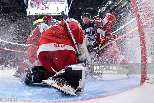 Goaltender Kasper Krog of Team Denmark makes a save while teammate David Madsen defends against Petrus Palmu of Team Finland during the IIHF World...