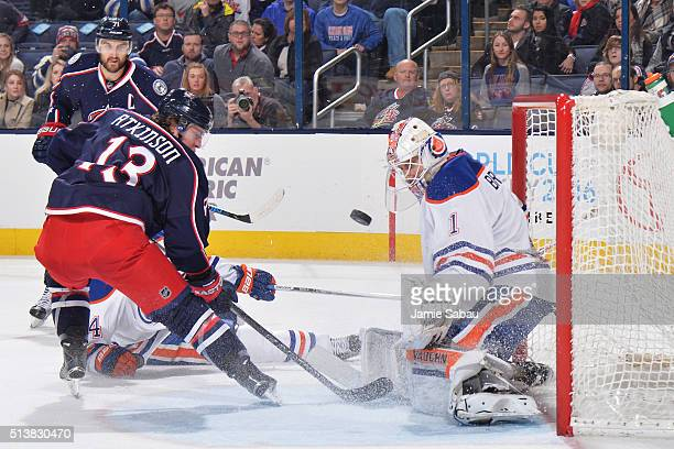 Goaltender Laurent Brossoit of the Edmonton Oilers defends the net as Cam Atkinson of the Columbus Blue Jackets crashes the net during the third...