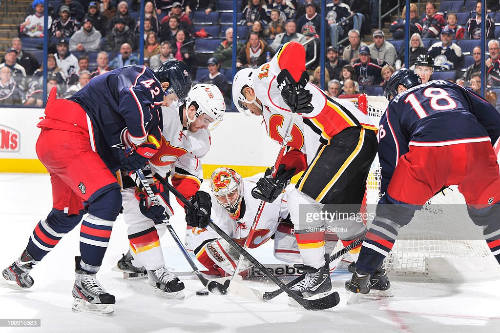 Goaltender Leland Irving #37 of the Calgary Flames keeps his eyes on the puck as T.J. Brodie #7 of the Calgary Flames and Jarome Iginla #12 of the Calgary Flames work to keep the puck away from Artem Anisimovand R.J. Umberger #18 of the Columbus Blue Jackets in overtime on February 7, 2013 at Nationwide Arena in Columbus, Ohio. Calgary defeated Columbus in overtime 4-3.