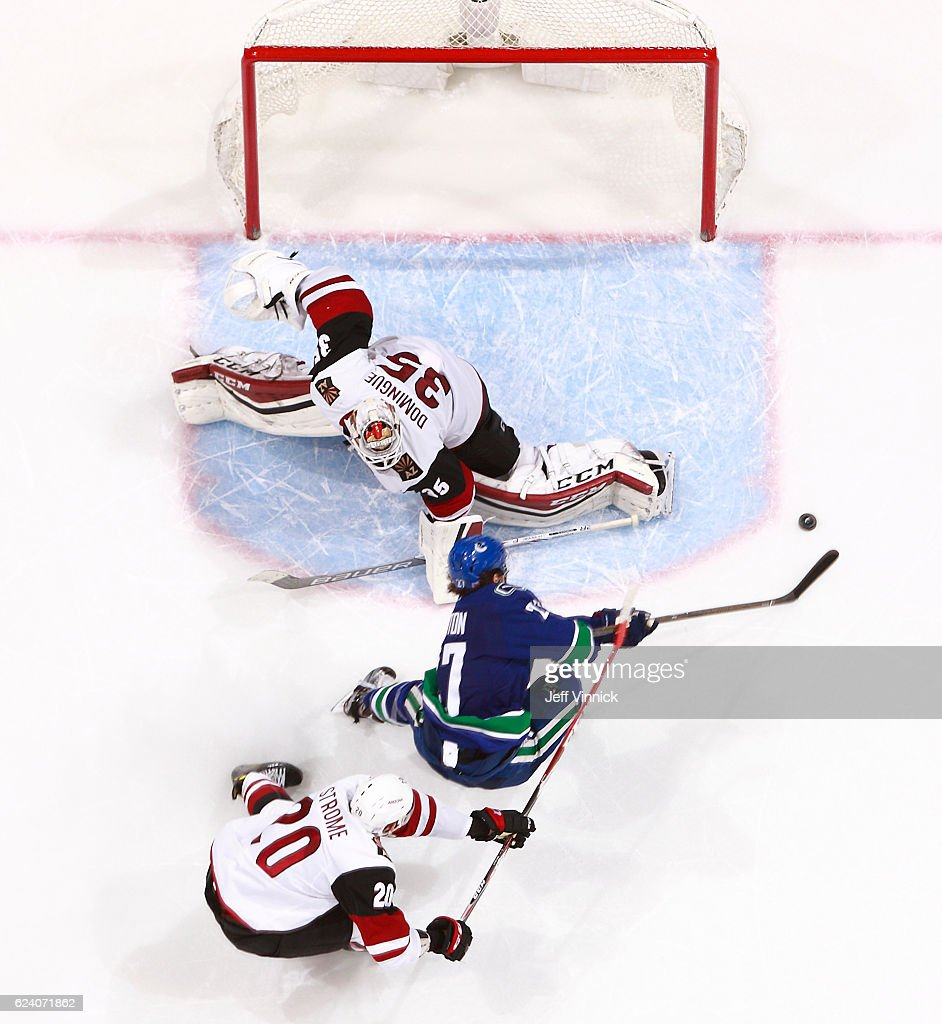 Goaltender Louis Domingue looks on as Dylan Strome #20 of the Arizona Coyotes hooks Ben Hutton #27 of the Vancouver Canucks during their NHL game at Rogers Arena November 17, 2016 in Vancouver, British Columbia, Canada. Vancouver won 3-2 in overtime. Hutton was a warded a penalty shot on the play.