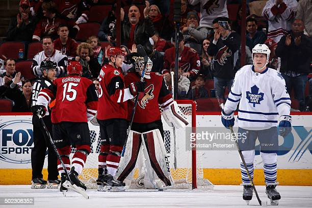 Goaltender Louis Domingue of the Arizona Coyotes is congratulated by Connor Murphy and Boyd Gordon after defeating the Toronto Maple Leafs 32 in the...