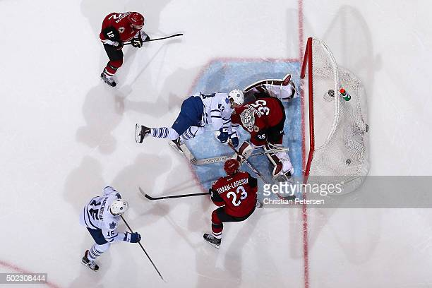 Goaltender Louis Domingue of the Arizona Coyotes looks for the puck as Shawn Matthias of the Toronto Maple Leafs skates into the crease during the...