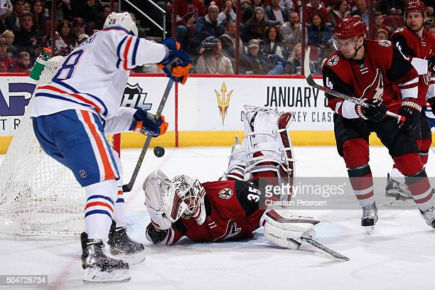 Goaltender Louis Domingue of the Arizona Coyotes makes a diving save on a shot as Lauri Korpikoski of the Edmonton Oilers looks for a rebound during...