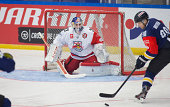 Goaltender Luka Gracnar of Salzburg makes a save as Ted Brithén of HV71 shots at goal during the Champions Hockey League group stage game between...