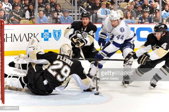 Goaltender MarcAndre Fleury of the Pittsburgh Penguins makes a stick save on a shot from Nate Thompson of the Tampa Bay Lightning as Brooks Orpik of...