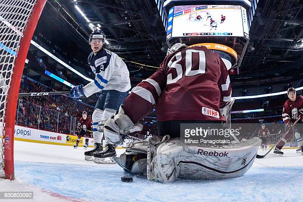 Goaltender Mareks Mitens of Team Latvia loses sight of the puck as Janne Kuokkanen of Team Finland skates by during the 2017 IIHF World Junior...