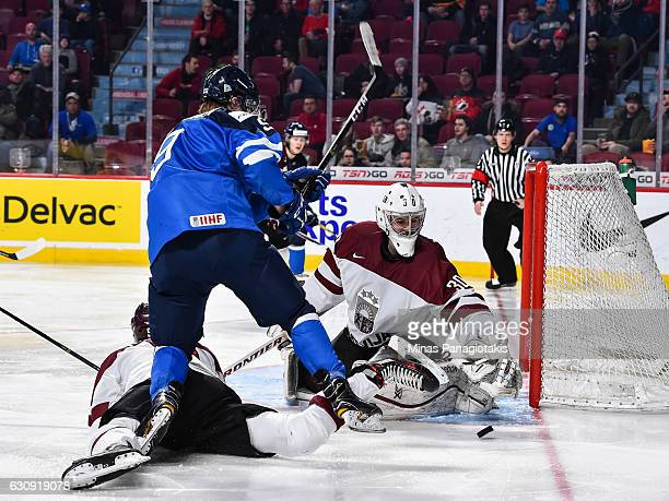 Goaltender Mareks Mitens of Team Latvia makes a save on a shot by Janne Kuokkanen of Team Finland during the 2017 IIHF World Junior Championship...
