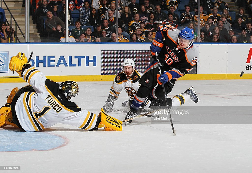 Goaltender <a gi-track='captionPersonalityLinkClicked' href=/galleries/search?phrase=Marty+Turco&family=editorial&specificpeople=202549 ng-click='$event.stopPropagation()'>Marty Turco</a> #1 of the Boston Bruins makes a sprawling save against <a gi-track='captionPersonalityLinkClicked' href=/galleries/search?phrase=Michael+Grabner&family=editorial&specificpeople=537955 ng-click='$event.stopPropagation()'>Michael Grabner</a> #40 of the New York Islanders on March 31, 2012 at Nassau Coliseum in Uniondale, New York.