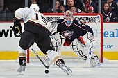 Goaltender Mathieu Garon of the Columbus Blue Jackets follows forward Ryan Getzlaf of the Anaheim Ducks as Getzlaf moves in for a shootout attempt on...