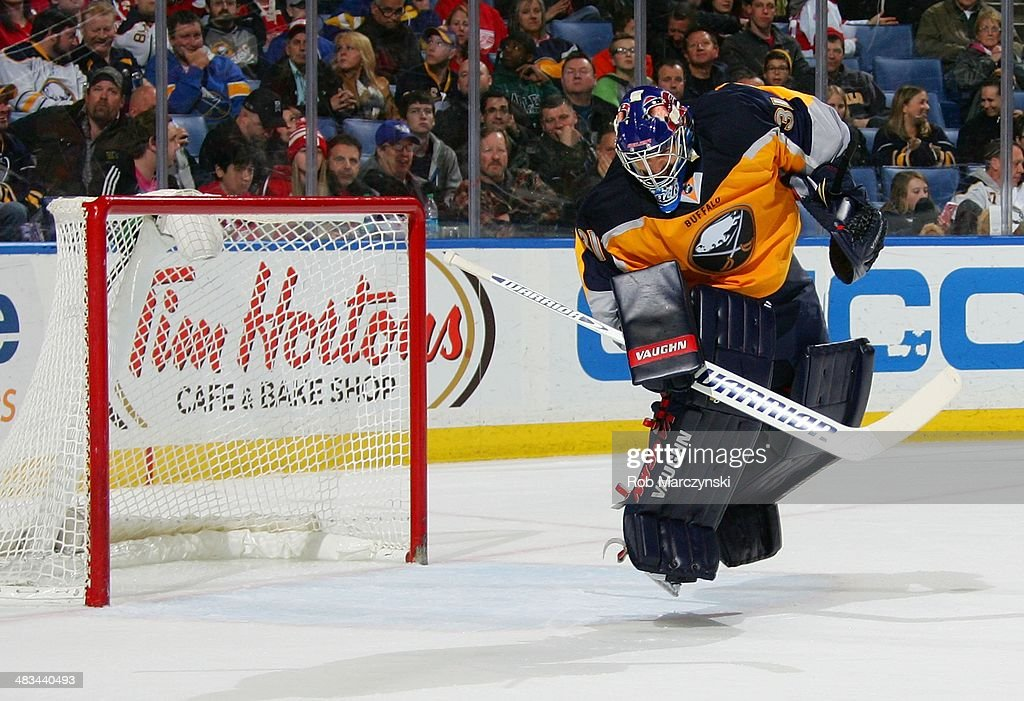 Goaltender <a gi-track='captionPersonalityLinkClicked' href=/galleries/search?phrase=Matt+Hackett&family=editorial&specificpeople=4161891 ng-click='$event.stopPropagation()'>Matt Hackett</a> #31 of the Buffalo Sabres jumps to deflect a puck on a shot from the Detroit Red Wings on April 8, 2014 at the First Niagara Center in Buffalo, New York.
