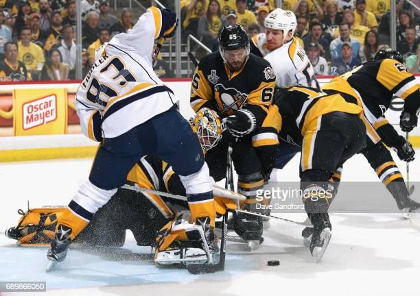 Goaltender Matt Murray of the Pittsburgh Penguins makes a save underneath Vernon Fiddler of the Nashville Predators as teammate Ron Hainsey looks on...
