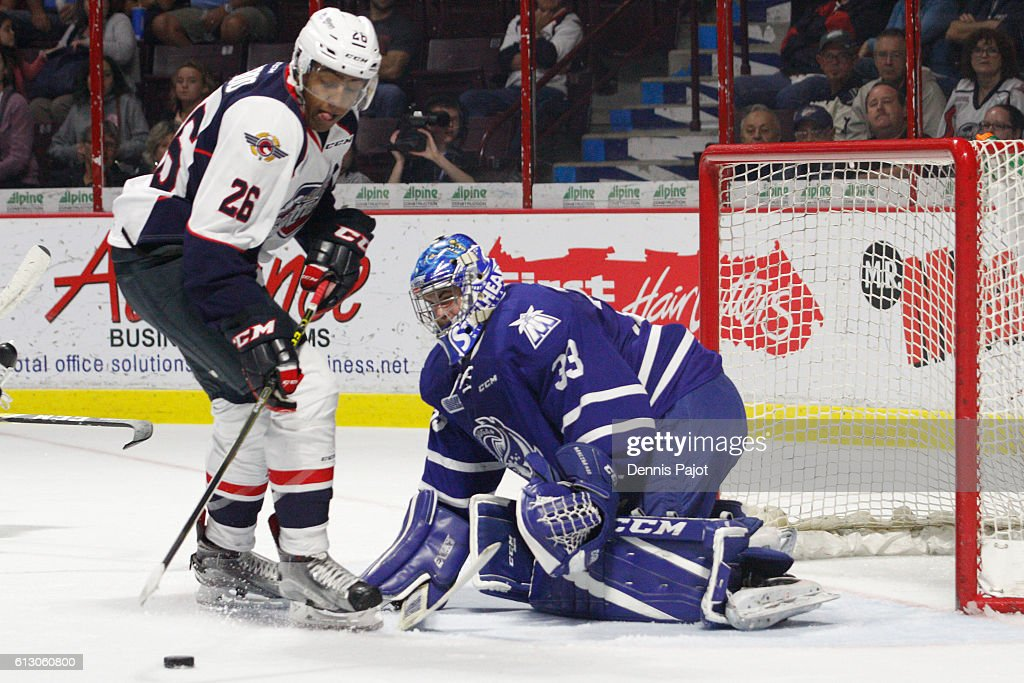 Goaltender Matthew Mancina #33 of the Mississauga Steelheads defends the net against forward Cole Purboo #26 of the Windsor Spitfires on October 6, 2016 at the WFCU Centre in Windsor, Ontario, Canada.