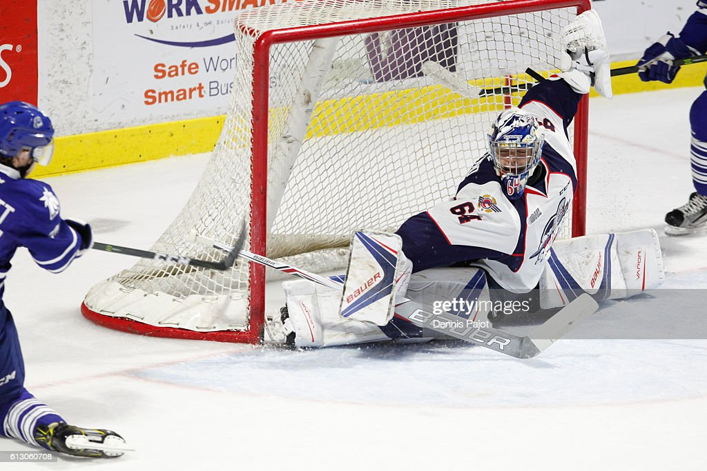 Goaltender Michael DiPietro #64 of the Windsor Spitfires makes a blocker save on a shot from forward Owen Tippett #74 of the Mississauga Steelheads on October 6, 2016 at the WFCU Centre in Windsor, Ontario, Canada.