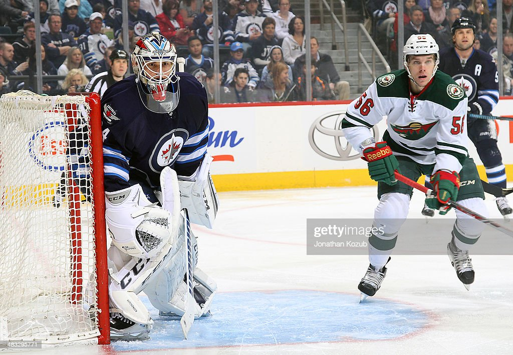 Goaltender Michael Hutchinson #34 of the Winnipeg Jets and Erik Haula #56 of the Minnesota Wild keep an eye on the play along the boards during first-period action at the MTS Centre on April 7, 2014 in Winnipeg, Manitoba, Canada.