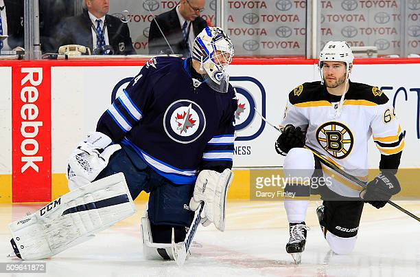 Goaltender Michael Hutchinson of the Winnipeg Jets and Tyler Randell of the Boston Bruins take part in the pregame warm up prior to NHL action at the...