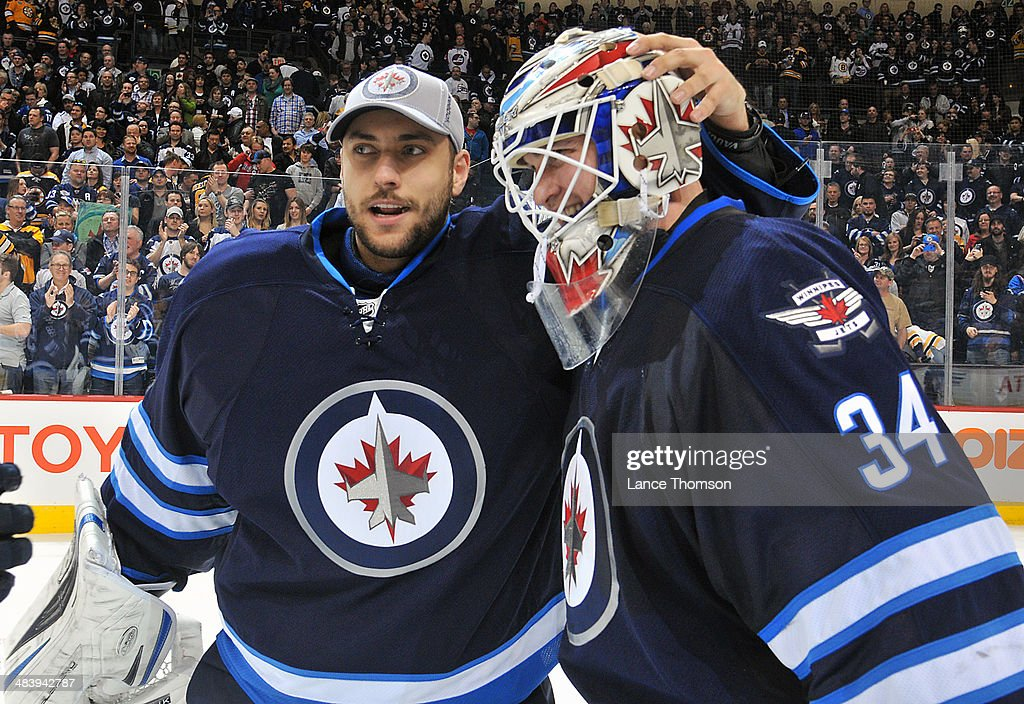 Goaltender Michael Hutchinson #34 of the Winnipeg Jets gets congratulated by teammate Ondrej Pavelec #31 after backstopping the Jets to a 2-1 shootout victory over the Boston Bruins in the final home game of the season at the MTS Centre on April 10, 2014 in Winnipeg, Manitoba, Canada.
