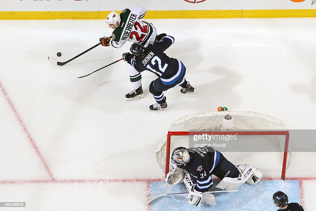 Goaltender Michael Hutchinson #34 of the Winnipeg Jets keeps an eye on the play behind the net as teammate <a gi-track='captionPersonalityLinkClicked' href=/galleries/search?phrase=Olli+Jokinen&family=editorial&specificpeople=202946 ng-click='$event.stopPropagation()'>Olli Jokinen</a> #12 defends against <a gi-track='captionPersonalityLinkClicked' href=/galleries/search?phrase=Nino+Niederreiter&family=editorial&specificpeople=6667732 ng-click='$event.stopPropagation()'>Nino Niederreiter</a> #22 of the Minnesota Wild during second-period action at the MTS Centre on April 7, 2014 in Winnipeg, Manitoba, Canada.