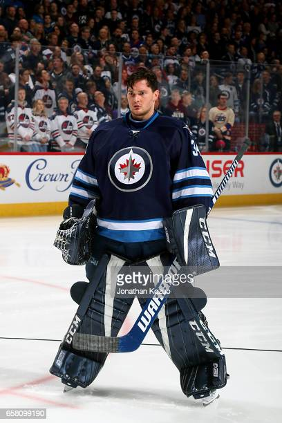 Goaltender Michael Hutchinson of the Winnipeg Jets looks on during the singing of 'O Canada' prior to puck drop against the Vancouver Canucks at the...