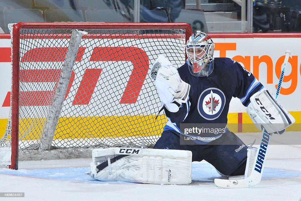 Goaltender Michael Hutchinson #34 of the Winnipeg Jets makes a glove save during the pre-game warm up prior to his NHL debut against the Minnesota Wild at the MTS Centre on April 7, 2014 in Winnipeg, Manitoba, Canada.