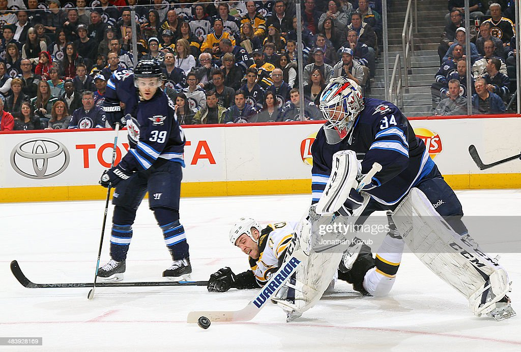Goaltender Michael Hutchinson #34 of the Winnipeg Jets plays the puck away from a fallen Gregory Campbell #11 of the Boston Bruins during second period action at the MTS Centre on April 10, 2014 in Winnipeg, Manitoba, Canada.