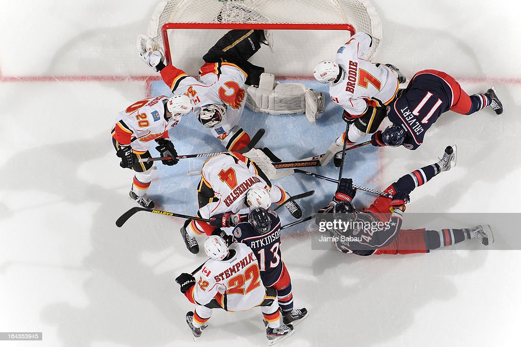Goaltender Miikka Kiprusoff #34 of the Calgary Flames covers the puck while Flames and Blue Jackets players scramble in front of the net on March 22, 2013 at Nationwide Arena in Columbus, Ohio.