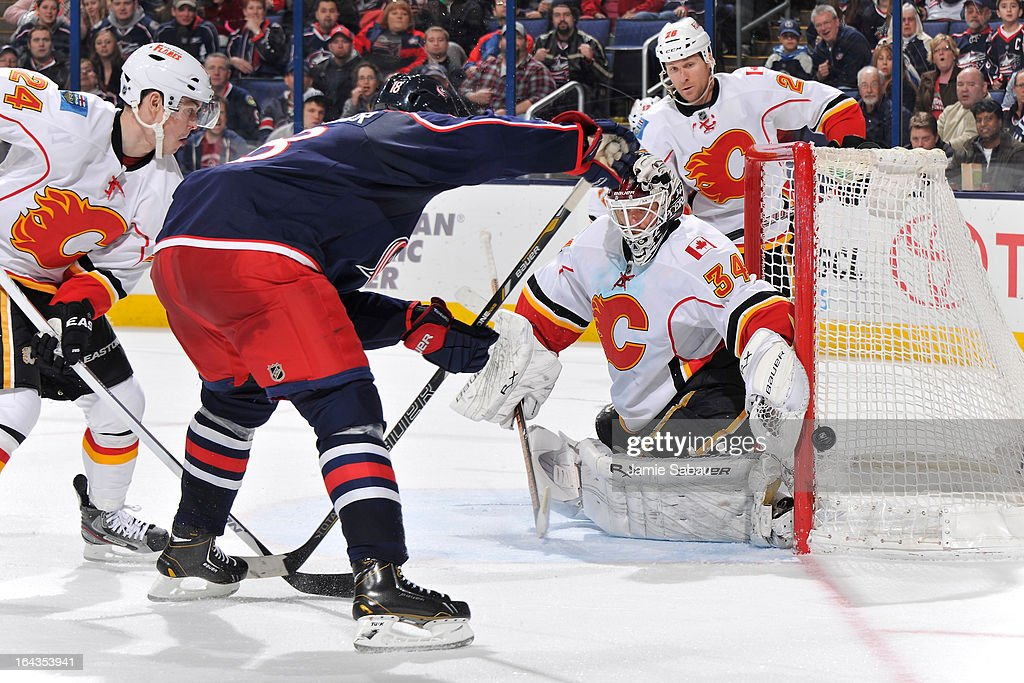 Goaltender Miikka Kiprusoff #34 of the Calgary Flames defends the net from a shot by R.J. Umberger #18 of the Columbus Blue Jackets during the third period on March 22, 2013 at Nationwide Arena in Columbus, Ohio. Columbus defeated Calgary 5-1.