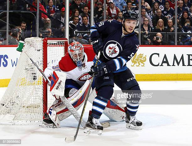 Goaltender Mike Condon of the Montreal Canadiens looks around a screen set by Marko Dano of the Winnipeg Jets during second period action at the MTS...