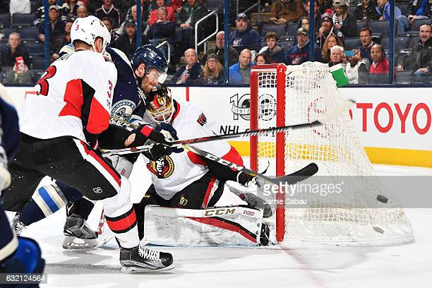 Goaltender Mike Condon of the Ottawa Senators defends the net as Marc Methot of the Ottawa Senators and Boone Jenner of the Columbus Blue Jackets...