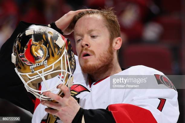 Goaltender Mike Condon of the Ottawa Senators puts on his mask during the first period of the NHL game against the Arizona Coyotes at Gila River...