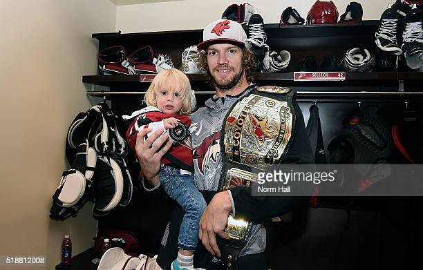 Goaltender Mike Smith of the Arizona Coyotes and his son hold the puck from his 30 shutout against the Washington Capitals at Gila River Arena on...