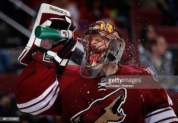 Goaltender Mike Smith of the Arizona Coyotes sprays water in his face during a break from the second period of the NHL game against the St Louis...