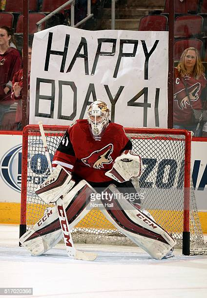 Goaltender Mike Smith of the Arizona Coyotes stands in goal as fans hold a happy birthday sign in the background before the start of a game against...