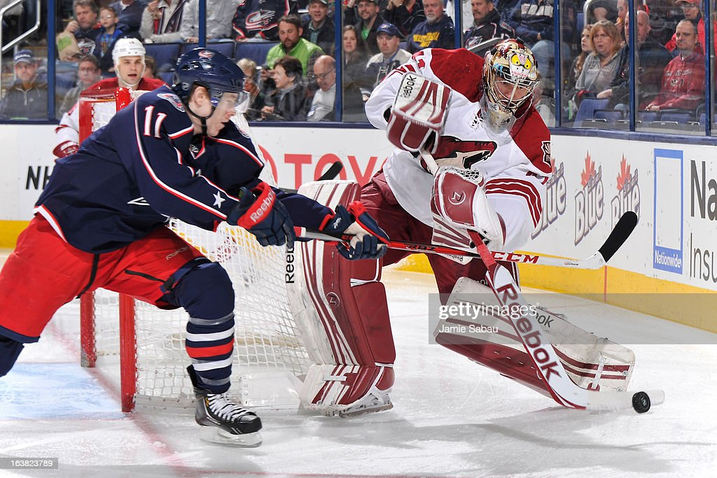 Goaltender Mike Smith #41 of the Phoenix Coyotes clears the puck past the defense of Matt Calvert #11 of the Columbus Blue Jackets during the first period on March 16, 2013 at Nationwide Arena in Columbus, Ohio.
