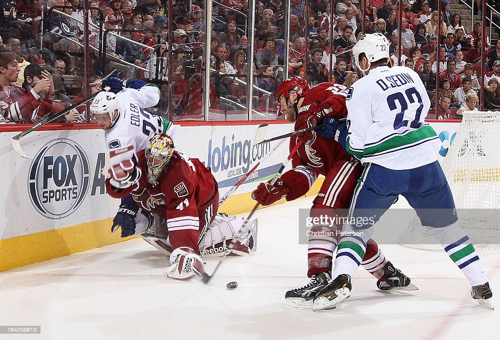 Goaltender Mike Smith #41 of the Phoenix Coyotes is hit from behind from <a gi-track='captionPersonalityLinkClicked' href=/galleries/search?phrase=Alexander+Edler&family=editorial&specificpeople=882987 ng-click='$event.stopPropagation()'>Alexander Edler</a> #23 of the Vancouver Canucks during the second period of the NHL game at Jobing.com Arena on March 21, 2013 in Glendale, Arizona. Edler received a 5 minute major penalty on the play.