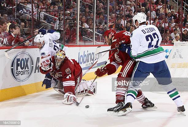 Goaltender Mike Smith of the Phoenix Coyotes is hit from behind from Alexander Edler of the Vancouver Canucks during the second period of the NHL...