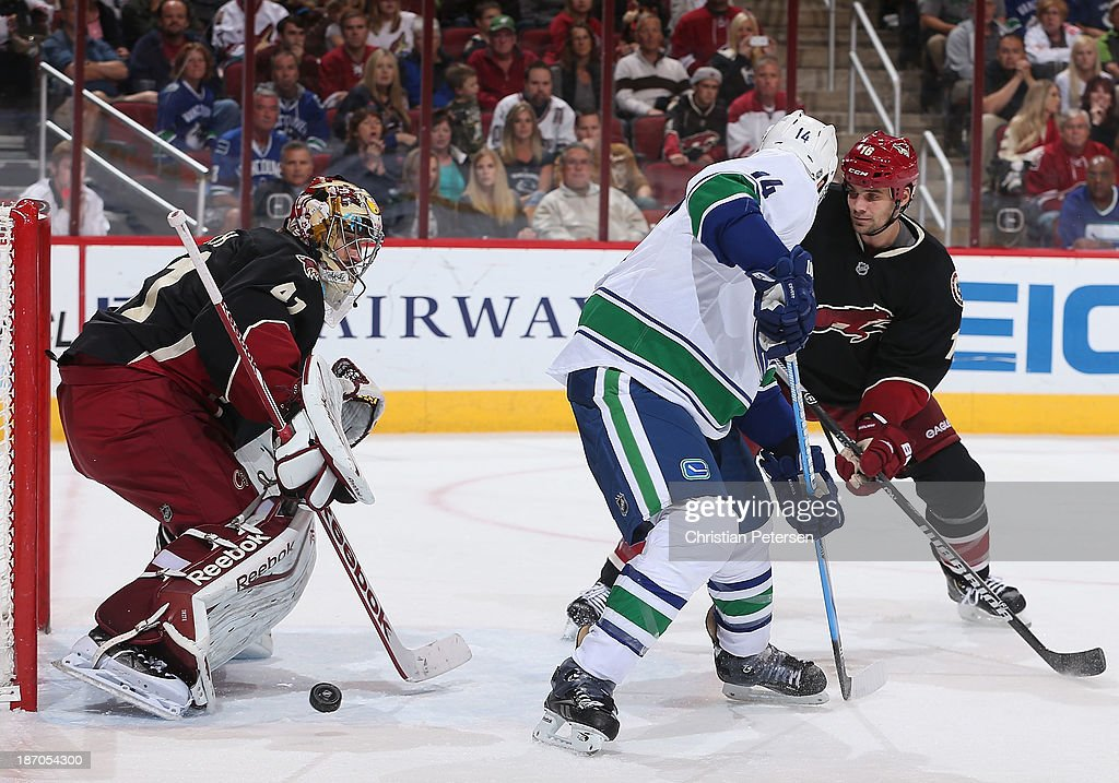 Goaltender Mike Smith #41 of the Phoenix Coyotes makes a pad save on the shot as Alex Burrows #14 of the Vancouver Canucks looks for a rebound during the NHL game at Jobing.com Arena on November 5, 2013 in Glendale, Arizona. The Coyotes defeated the Canucks 3-2 in an overtime shoot out.