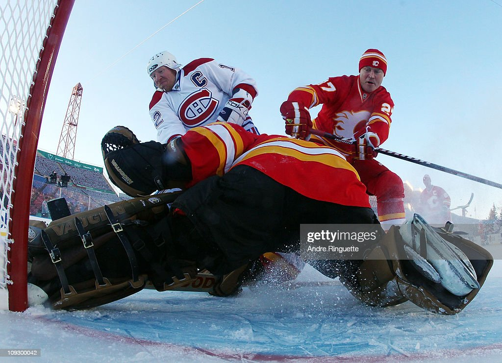 Goaltender Mike Vernon #30 and Brian MacLellan #27 of the Calgary Flames Alumni defend the net against Mike Keane #12 of the Montreal Canadiens Alumni during the Alumni game held as part of the 2011 NHL Heritage Classic festivities at McMahon Stadium on February 19, 2011 in Calgary, Alberta, Canada.