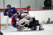 Goaltender Nathan Lieuwen of the Buffalo Sabres is run into by teammate Alex Biega and Carl Hagelin of the New York Rangers during the NHL Prospects...