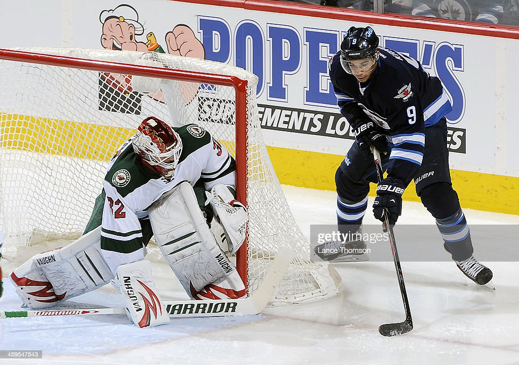 Goaltender Niklas Backstrom #32 of the Minnesota Wild hugs the post as <a gi-track='captionPersonalityLinkClicked' href=/galleries/search?phrase=Evander+Kane&family=editorial&specificpeople=4303789 ng-click='$event.stopPropagation()'>Evander Kane</a> #9 of the Winnipeg Jets plays the puck to the side of the net during second period action at the MTS Centre on December 27, 2013 in Winnipeg, Manitoba, Canada.