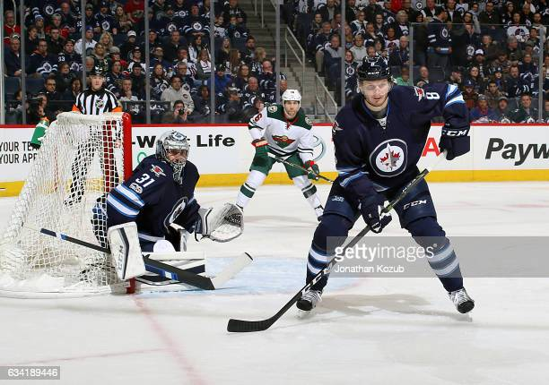 Goaltender Ondrej Pavelec Jacob Trouba of the Winnipeg Jets and Jason Zucker of the Minnesota Wild keep an eye on the play during first period action...