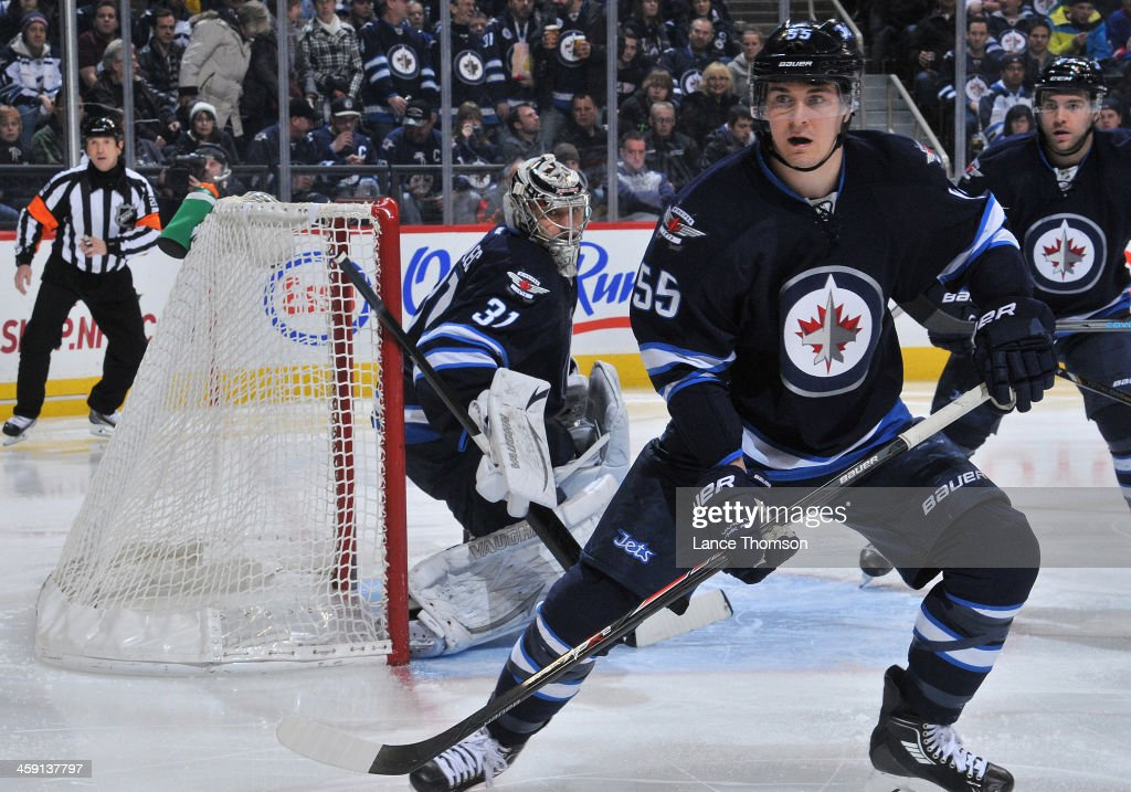Goaltender Ondrej Pavelec Mark Scheifele and Grant Clitsome of the Winnipeg Jets keep an eye on the play along the corner boards during third period...