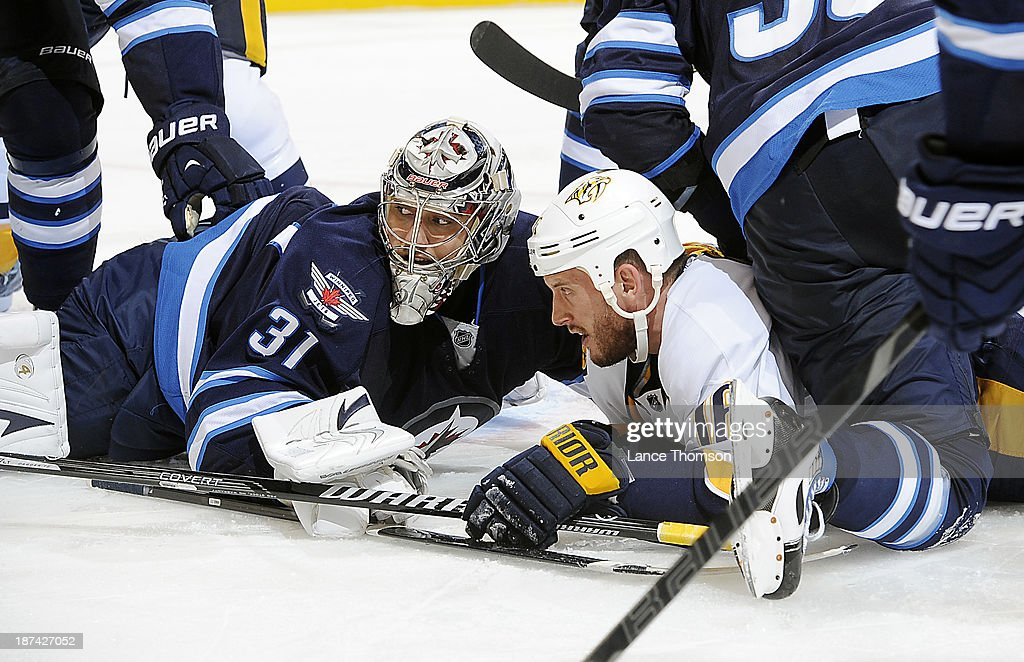 Goaltender Ondrej Pavelec #31 of the Winnipeg Jets and Rich Clune #16 of the Nashville Predators sprawl on the ice at the bottom of the pile up during third period action at the MTS Centre on November 8, 2013 in Winnipeg, Manitoba, Canada.