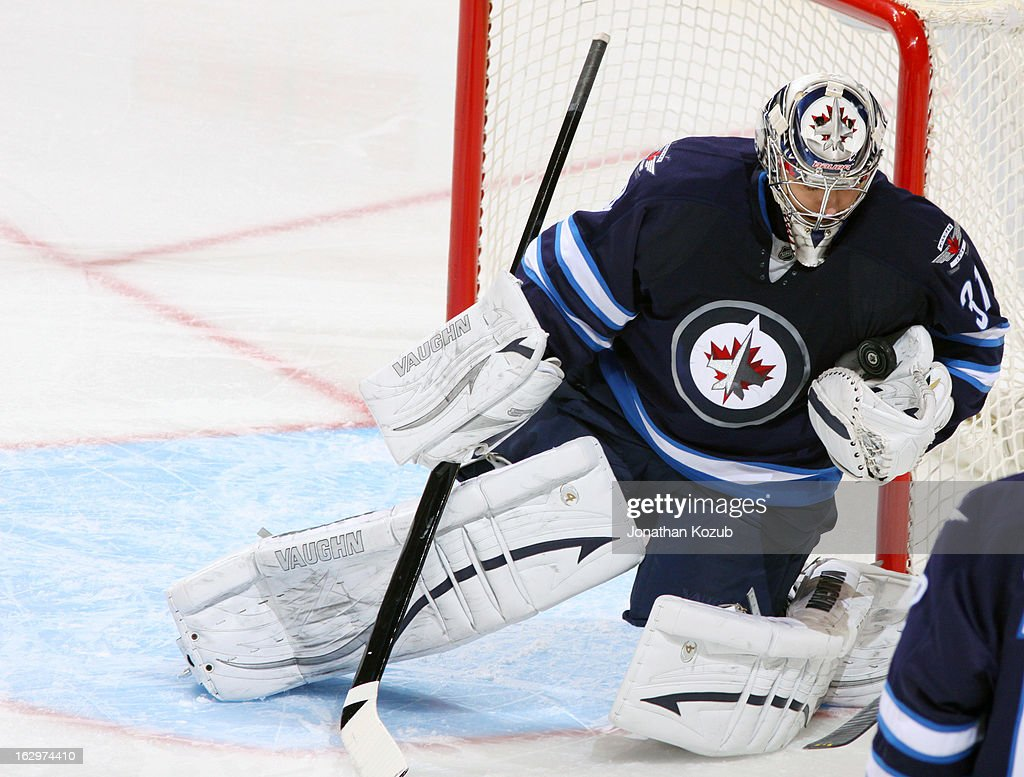 Goaltender Ondrej Pavelec #31 of the Winnipeg Jets catches the puck in his glove as he guards the post during second period action against the Washington Capitals at the MTS Centre on March 2, 2013 in Winnipeg, Manitoba, Canada.