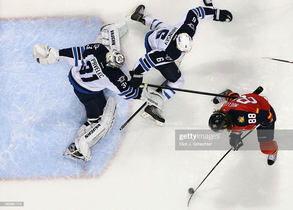 Goaltender Ondrej Pavelec #31 of the Winnipeg Jets defends the net with the help of teammate <a gi-track='captionPersonalityLinkClicked' href=/galleries/search?phrase=Ron+Hainsey&family=editorial&specificpeople=206345 ng-click='$event.stopPropagation()'>Ron Hainsey</a> #6 against Peter Mueller #88 of the Florida Panthers at the BB&T Center on March 8, 2013 in Sunrise, Florida.