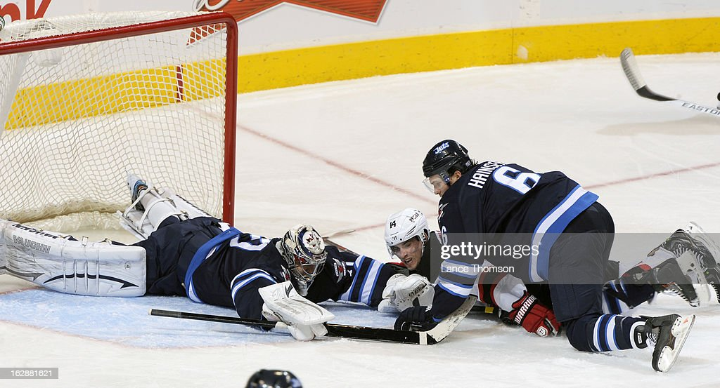 Goaltender Ondrej Pavelec #31 of the Winnipeg Jets flops on top of the puck in the crease as teammate Ron Hainsey #6 takes down Adam Henrique #14 of the New Jersey Devils during second period action at the MTS Centre on February 28, 2013 in Winnipeg, Manitoba, Canada.