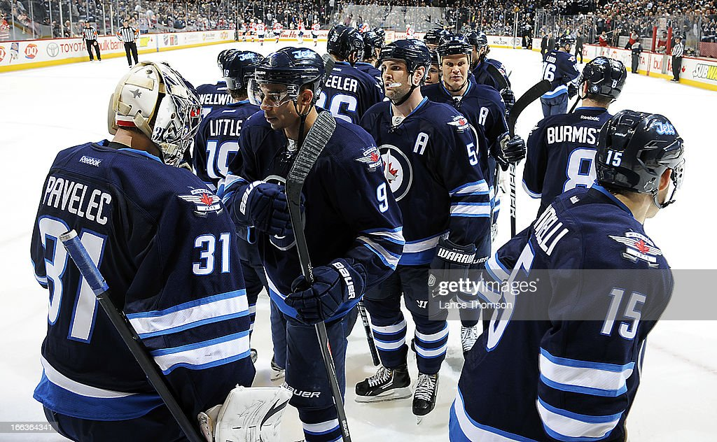 Goaltender Ondrej Pavelec #31 of the Winnipeg Jets gets congratulated by teammates after backstopping the Jets to a 7-2 victory over the Florida Panthers at the MTS Centre on April 11, 2013 in Winnipeg, Manitoba, Canada.