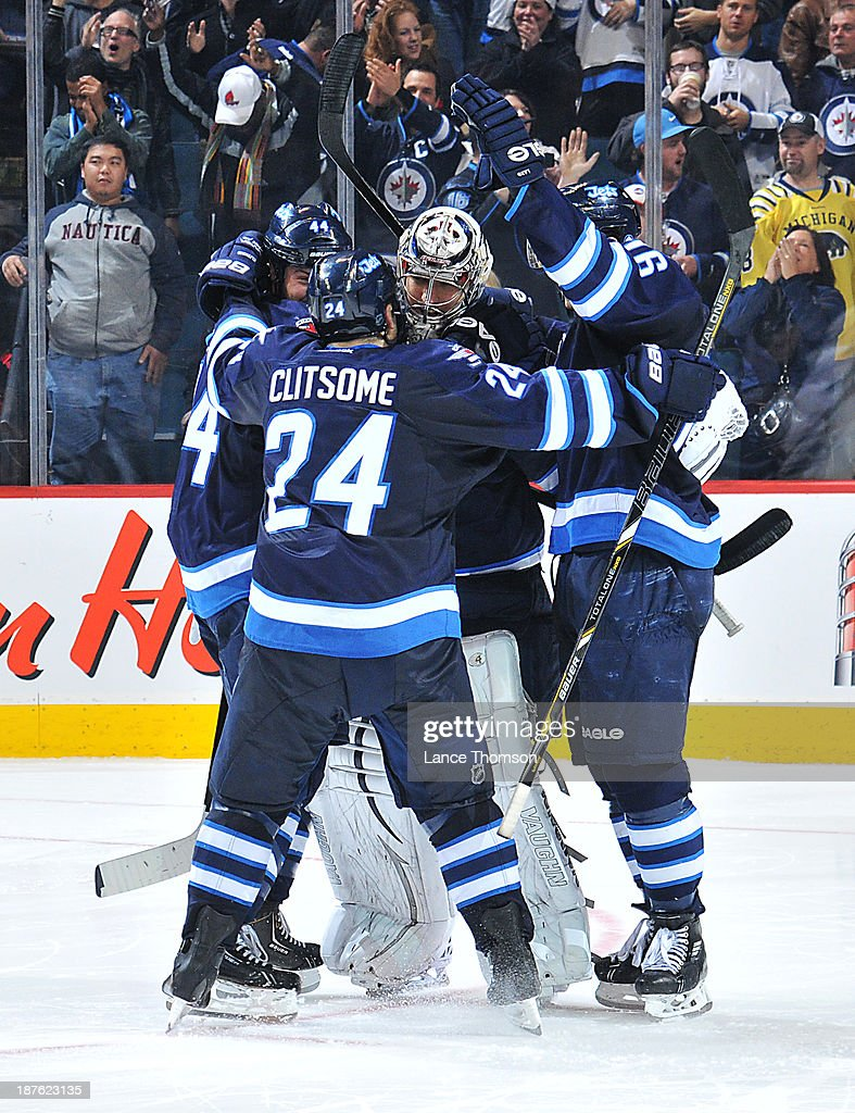 Goaltender Ondrej Pavelec #31 of the Winnipeg Jets gets mobbed by teammates <a gi-track='captionPersonalityLinkClicked' href=/galleries/search?phrase=Zach+Bogosian&family=editorial&specificpeople=4195061 ng-click='$event.stopPropagation()'>Zach Bogosian</a> #44, <a gi-track='captionPersonalityLinkClicked' href=/galleries/search?phrase=Grant+Clitsome&family=editorial&specificpeople=4596638 ng-click='$event.stopPropagation()'>Grant Clitsome</a> #24 and <a gi-track='captionPersonalityLinkClicked' href=/galleries/search?phrase=Andrew+Ladd&family=editorial&specificpeople=228452 ng-click='$event.stopPropagation()'>Andrew Ladd</a> #16 after backstopping the team to a 5-4 shootout victory over the San Jose Sharks at the MTS Centre on November 10, 2013 in Winnipeg, Manitoba, Canada.